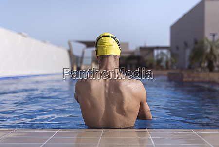 shirtless male swimmer in swimming pool