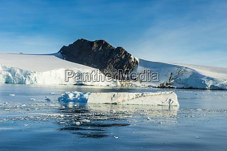 huge rock sticking out of glacier