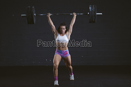 young woman practicing barbell squat at