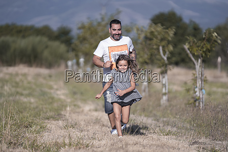 father running behind his little daughter