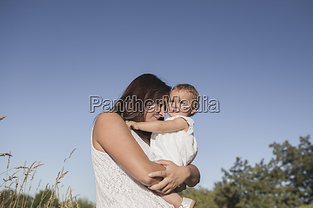 woman carrying her cute baby girl