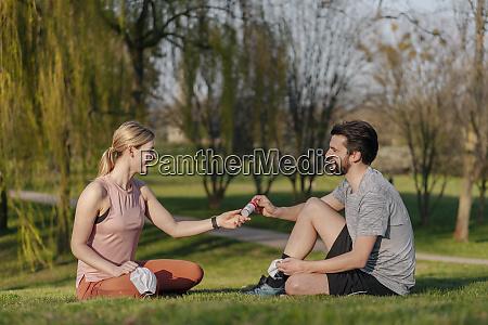 smiling man giving hand sanitizer to