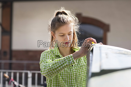 young woman throwing garbage in recycling
