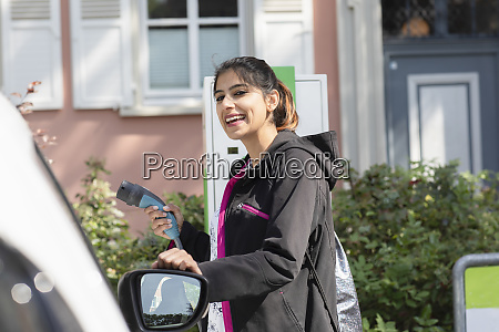happy woman holding electric plug by