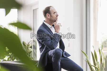 pensive businessman looking out of window
