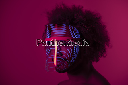 serious young man wearing led mask