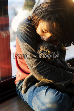 boy cuddling cat at home