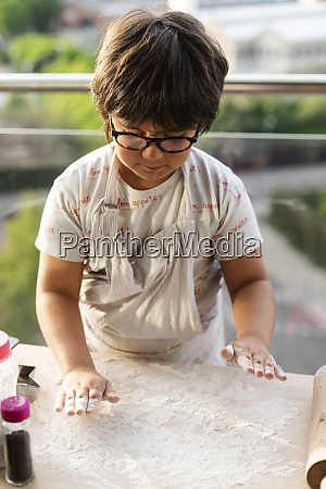 little boy spreading flour on kitchen
