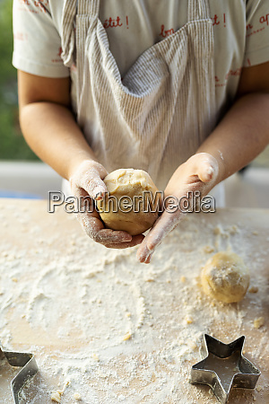 crop view of boy kneading dough