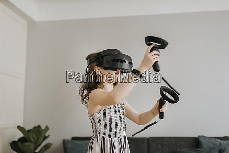 girl wearing virtual reality simulator playing