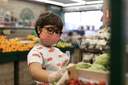 boy taking vegetables in supermarket