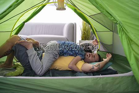 father and son tussling in tent