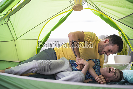 father and son playing in tent