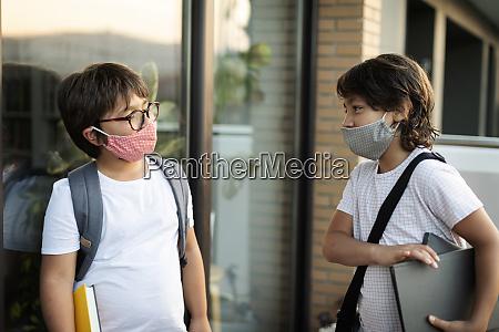 siblings wearing masks outdoors