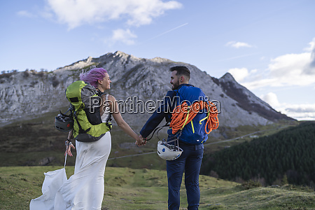 bridal couple with climbing backpacks at