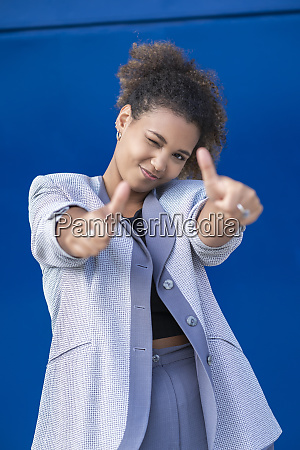 smiling businesswoman with thumbs up in