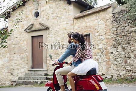 couple enjoying road trip on vespa