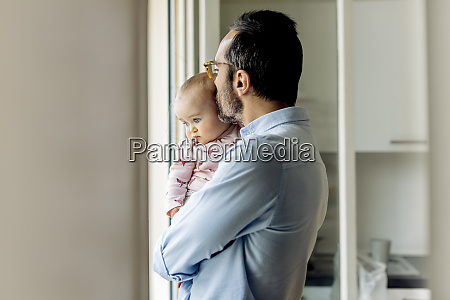 father with baby looking out of