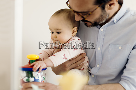 father holding baby girl playing with