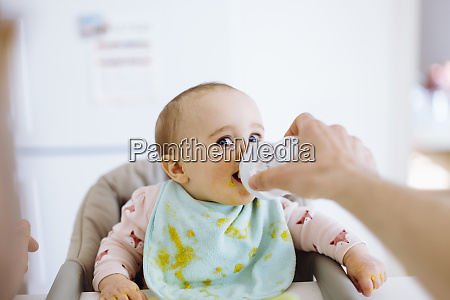 father holding bottle with water for