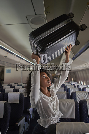 young woman positioning luggage inside storage
