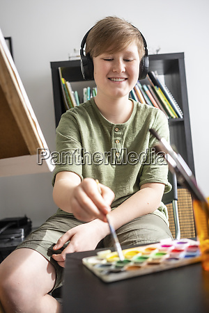 boy painting at easel and listening