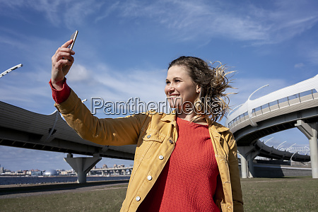 happy woman with windswept hair taking