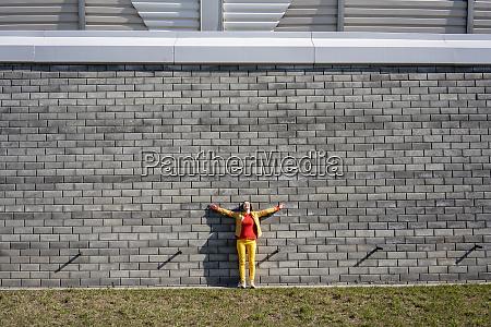 woman standing at a brick wall