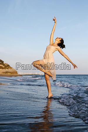delicate ballerina dancing on the beach