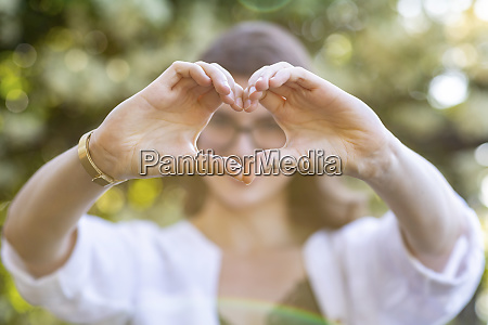 young woman forming a heart with