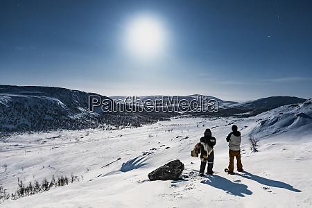 snowshoe hikers standing in winter landscape