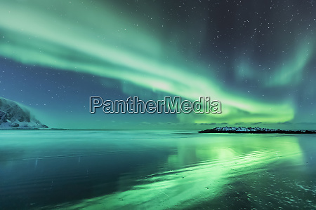northern lights above the beach berlevag