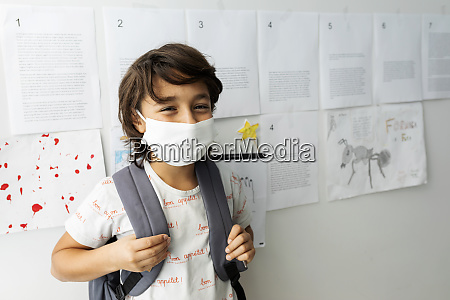 boy wearing mask standing against papers