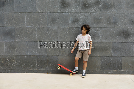 boy playing with skateboard while standing