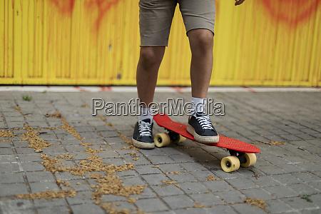 legs of boy skateboarding on footpath