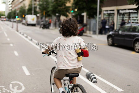 boy holding skateboard while riding bicycle