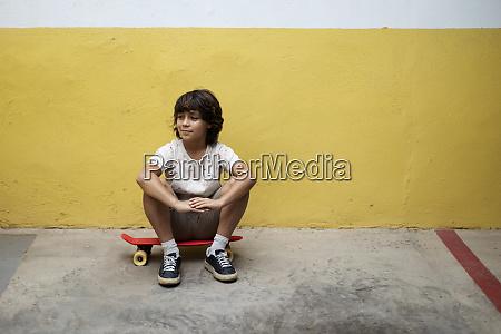 thoughtful boy sitting on skateboard against
