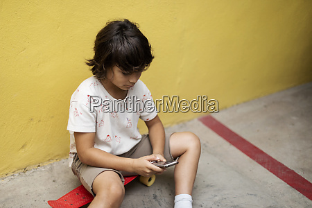 boy using mobile phone while sitting