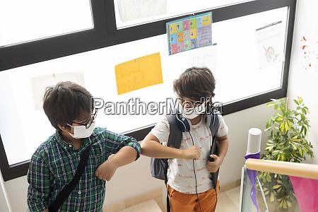 schoolboys wearing masks giving elbow bump