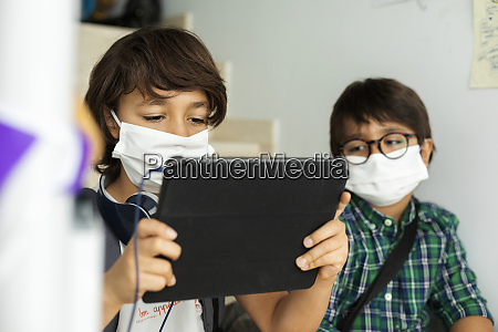 boy wearing face mask using digital