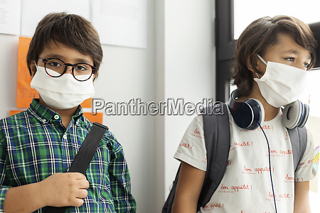 boy wearing mask standing with friend