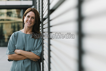 smiling redheaded woman leaning on wall