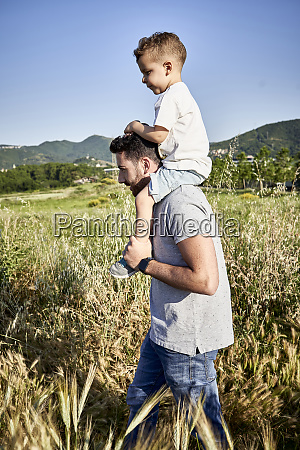 father carrying son on shoulders while