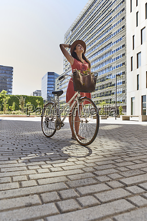 thoughtful woman standing with bicycle on