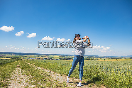 young woman playing golf at countryside