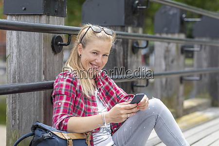 smiling mid adult woman using smart