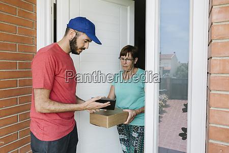 postal worker showing digital tablet to