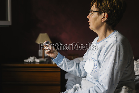 ill senior woman looking at thermometer
