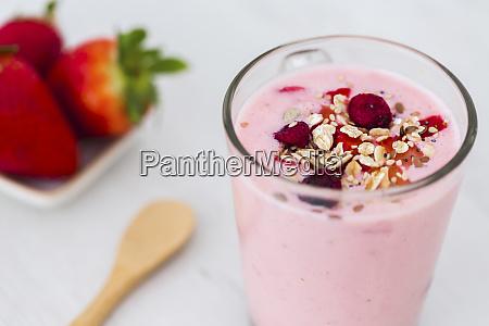 glass of strawberry milkshake with cereals
