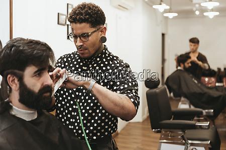 trendy hairdresser styling mans hair at